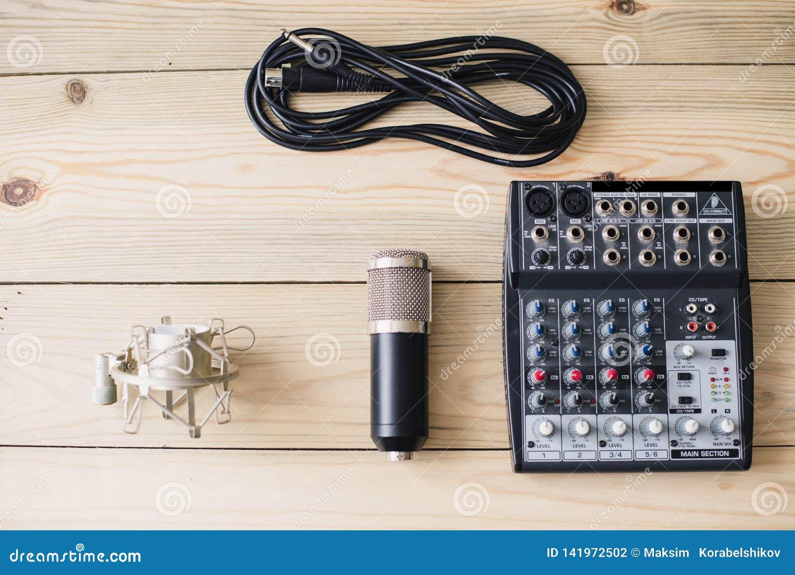 Microfone do portátil do estúdio e console de mistura no fundo de madeira