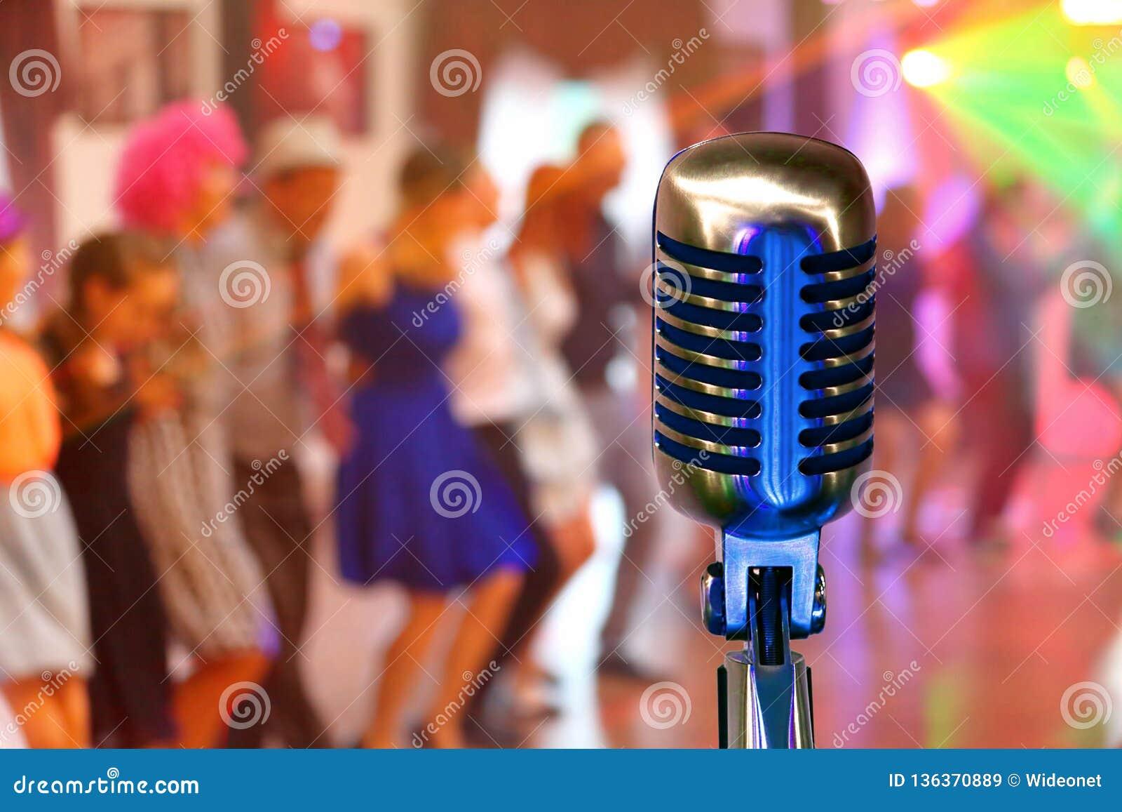 Microfone retro no concerto com os povos de dança da multidão e espaço vazio para o texto