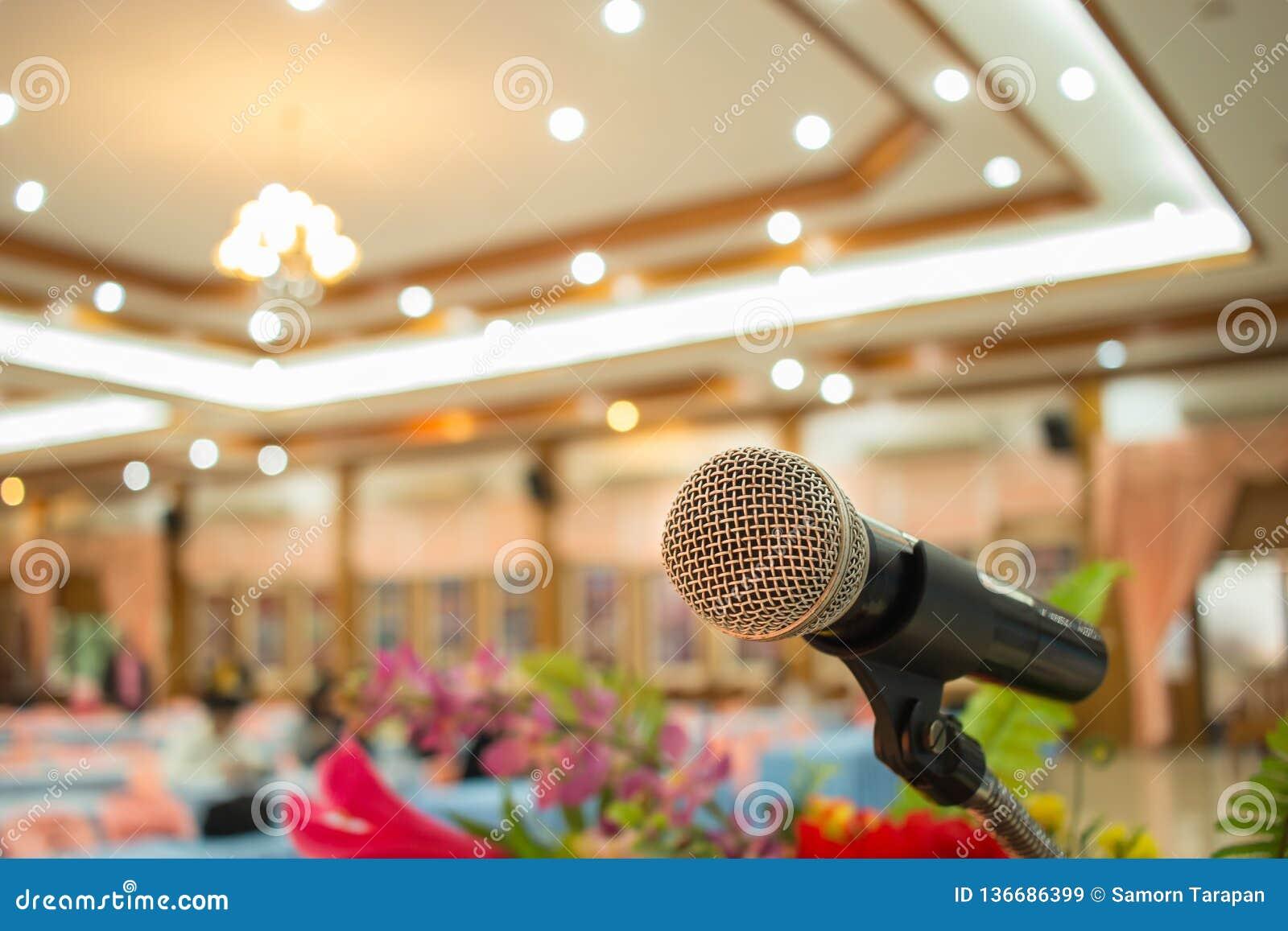 Microfones em abstrato borrados do discurso na luz faladora da sala de seminário ou da sala de conferências da parte dianteira, c
