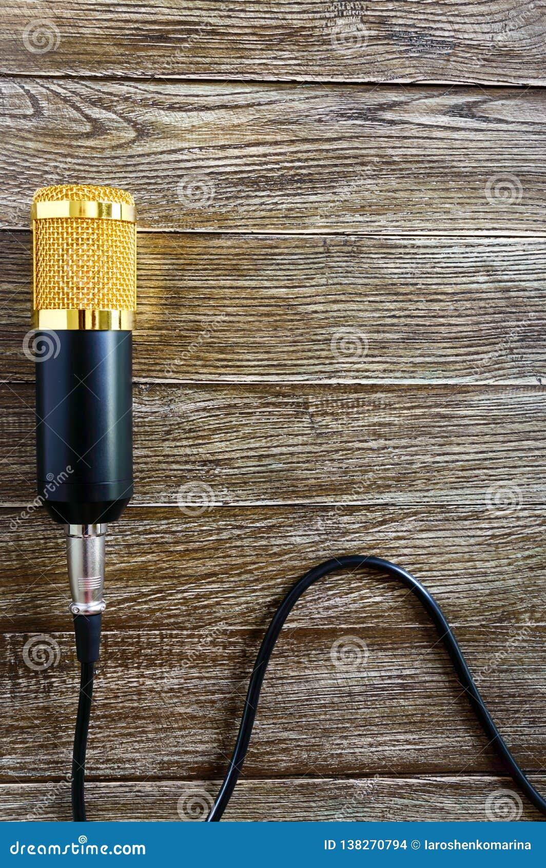 Microfono dell oro del condensatore con le bugie del cavo su una tavola di legno con lo spazio della copia Tema musicale Disposiz