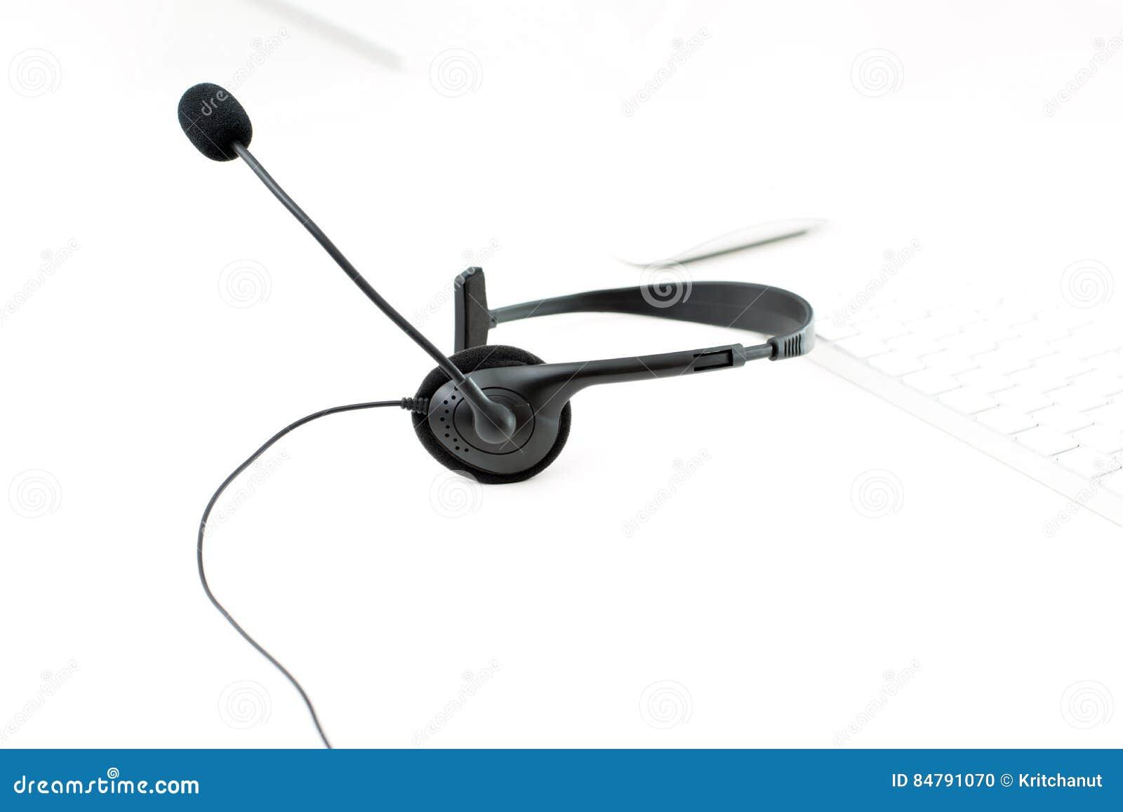 Microfoonhoofdtelefoon op witte lijst met het toetsenbordachtergrond van de onduidelijk beeldcomputer
