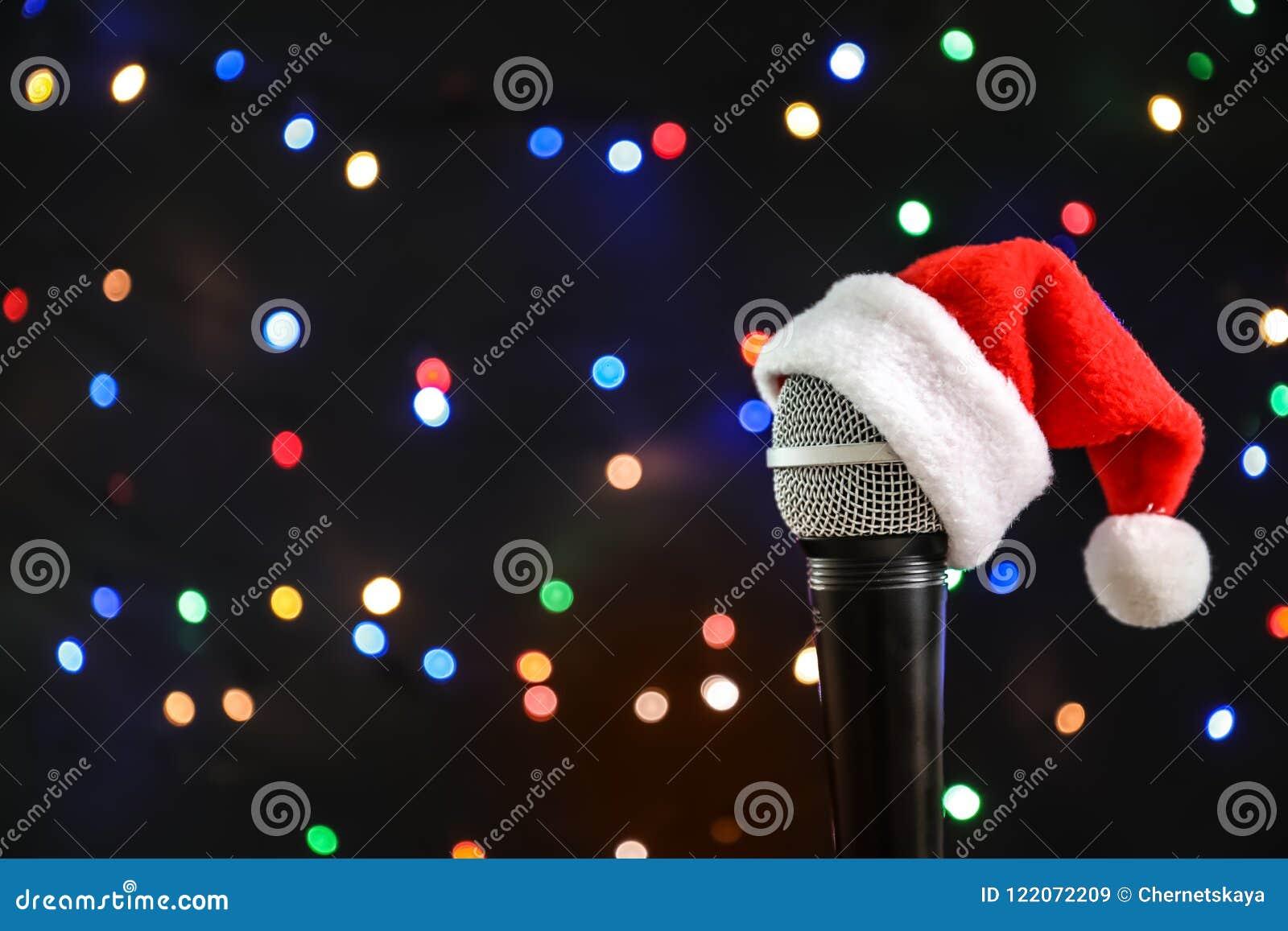 Microphone avec le chapeau de Santa contre les lumières brouillées