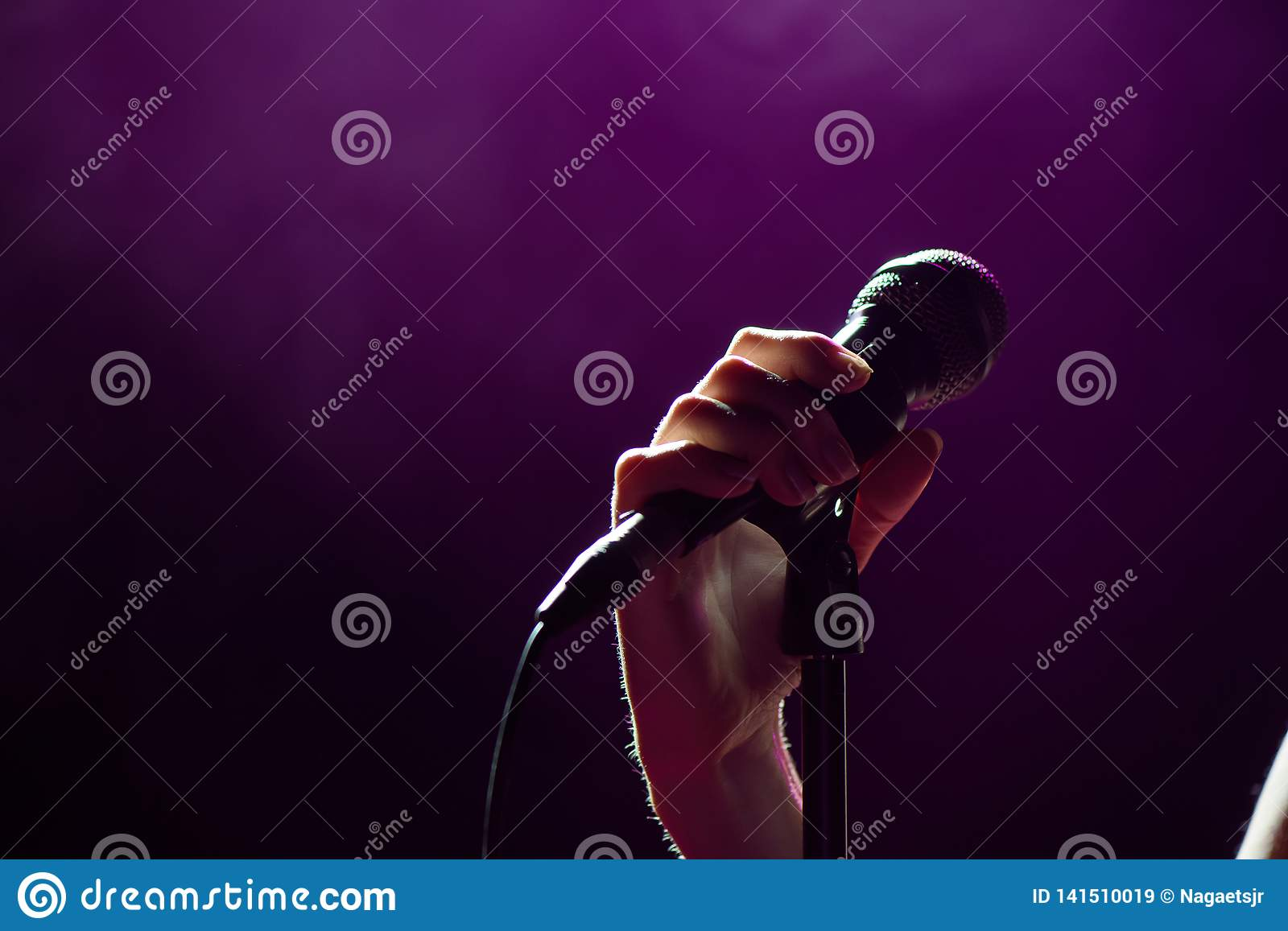 Microphone in hand singer on stage. Live music background. Microphone and stage lights.