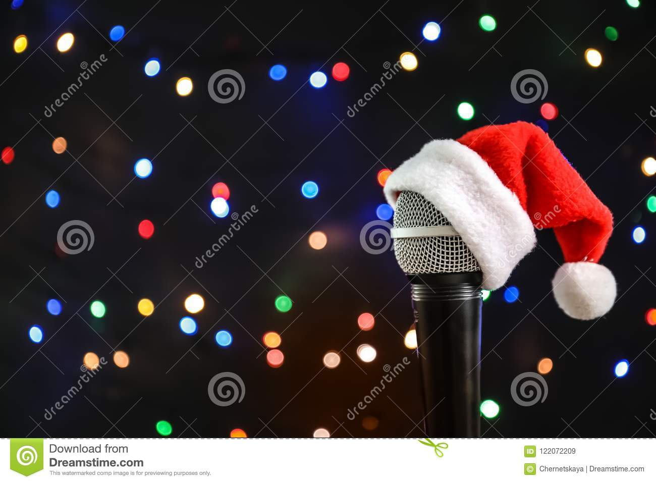 7cdb3abf77410 Microphone with Santa hat against blurred lights. Christmas music concept