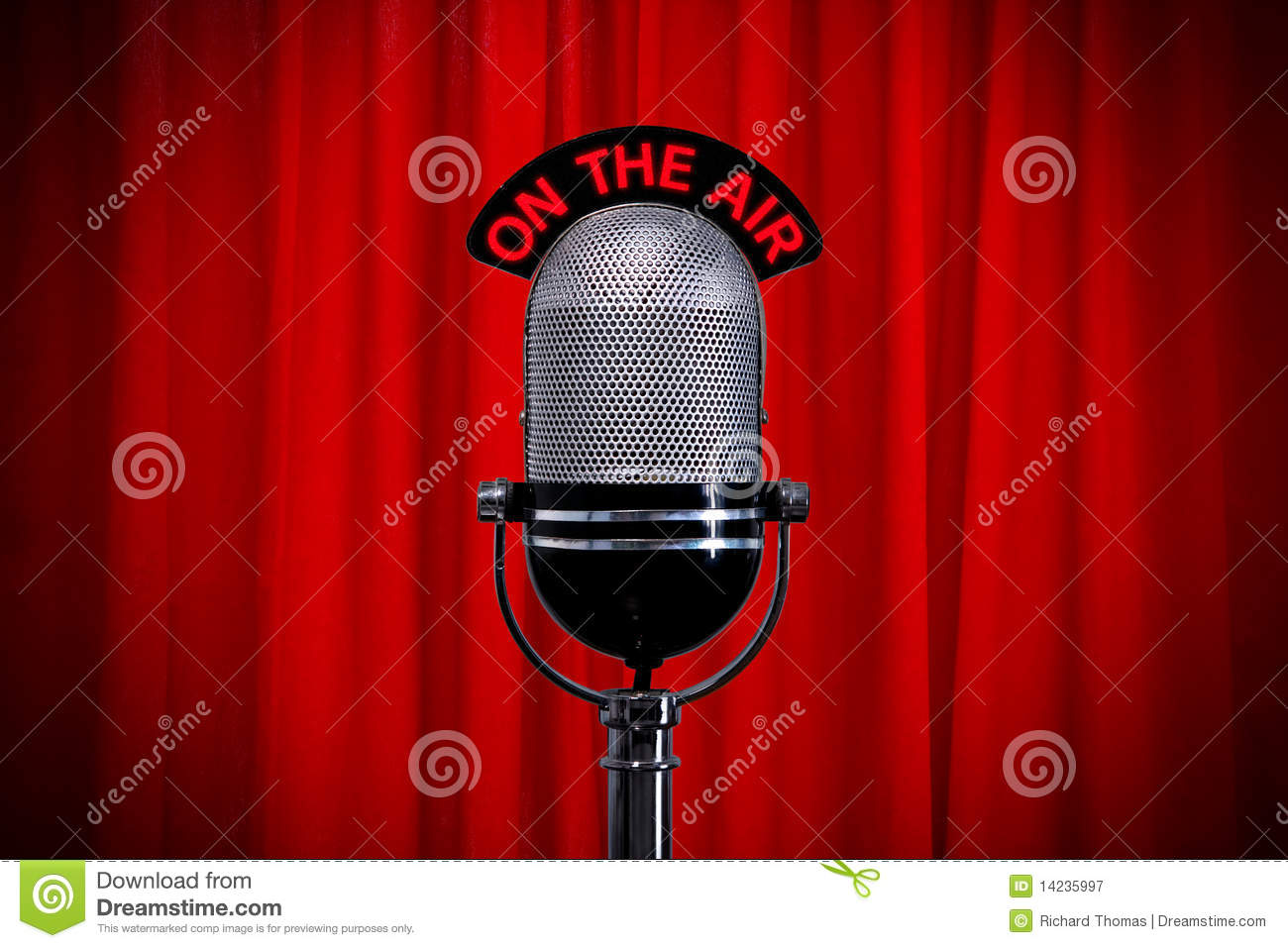 Microphone on stage with spotlight on red curtain