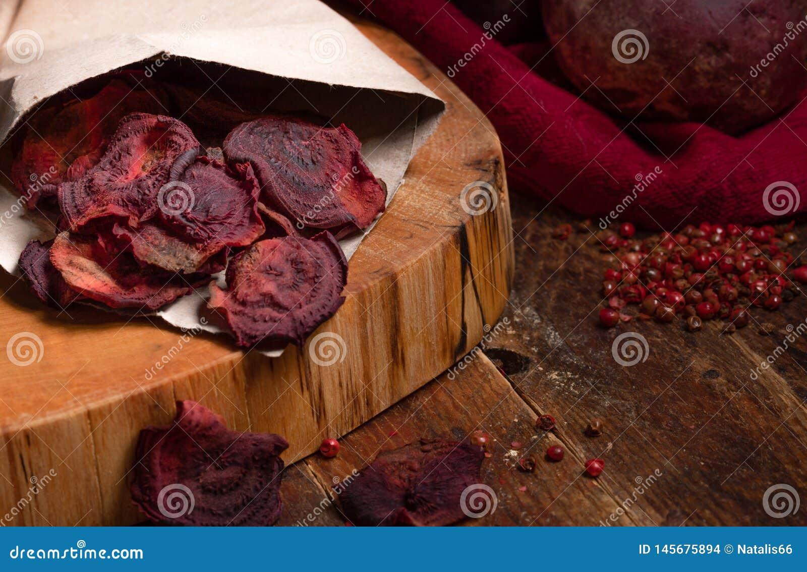 Microplaquetas caseiros das beterrabas no saco de papel no corte na tabela de madeira
