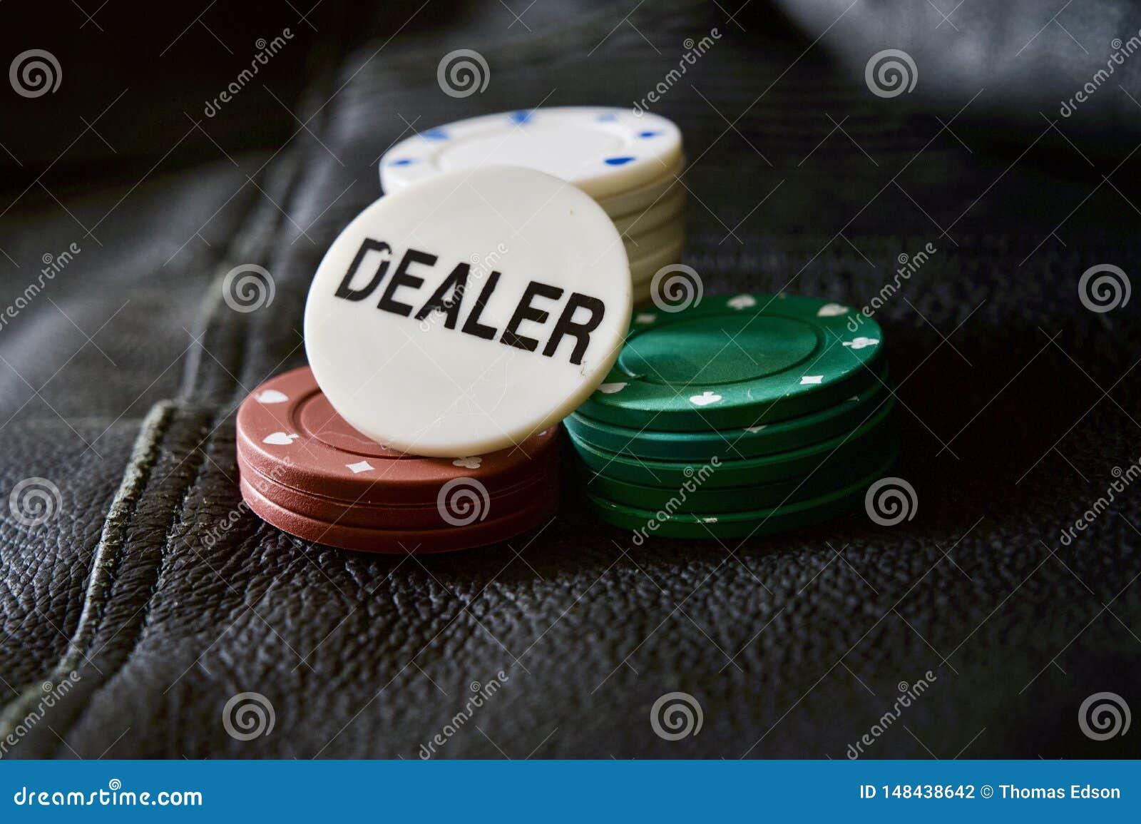 Microplaquetas de pôquer com a microplaqueta do negociante em fundo Textured