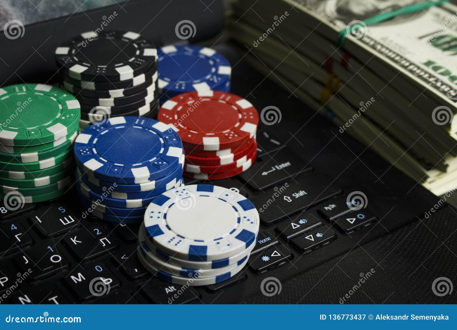 Microplaquetas de pôquer e blocos dos dólares em um portátil