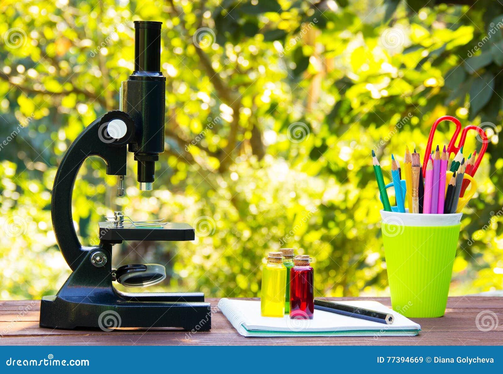 Microscoop en kantoorbehoeften op houten lijst glasflessen