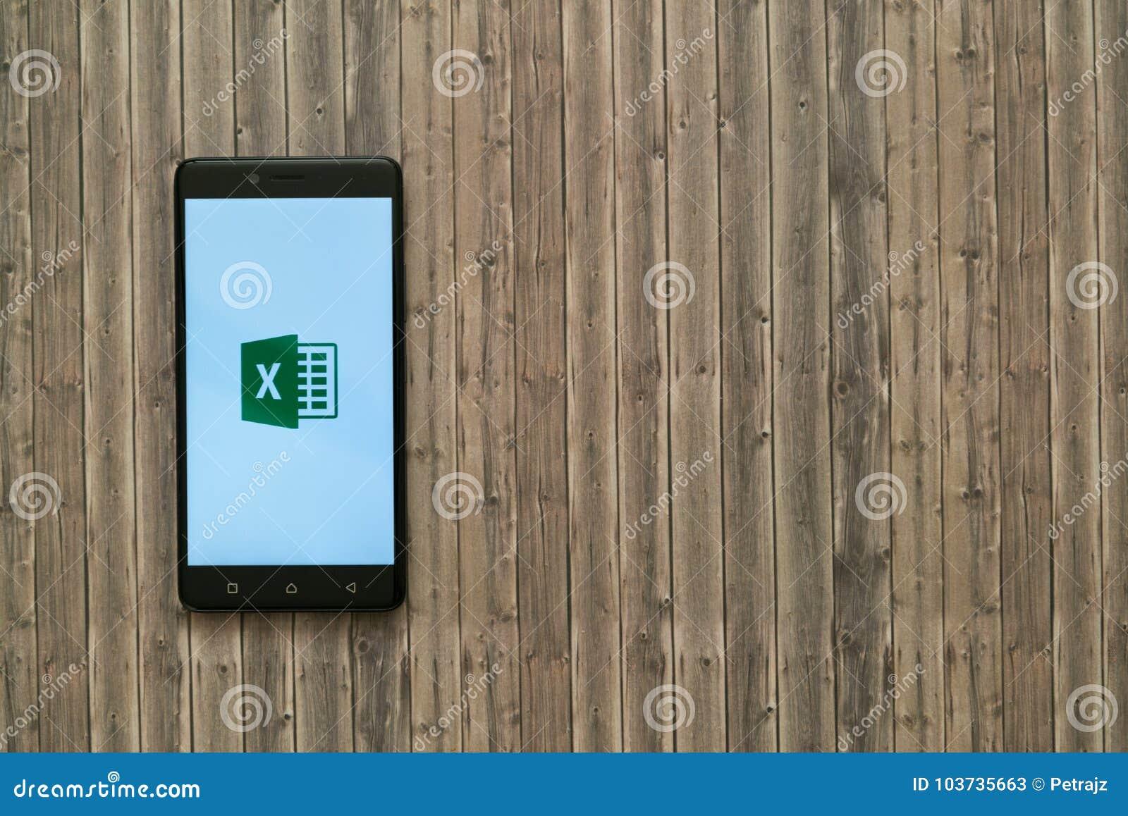 Microsoft Office przoduje loga na smartphone ekranie na drewnianym tle