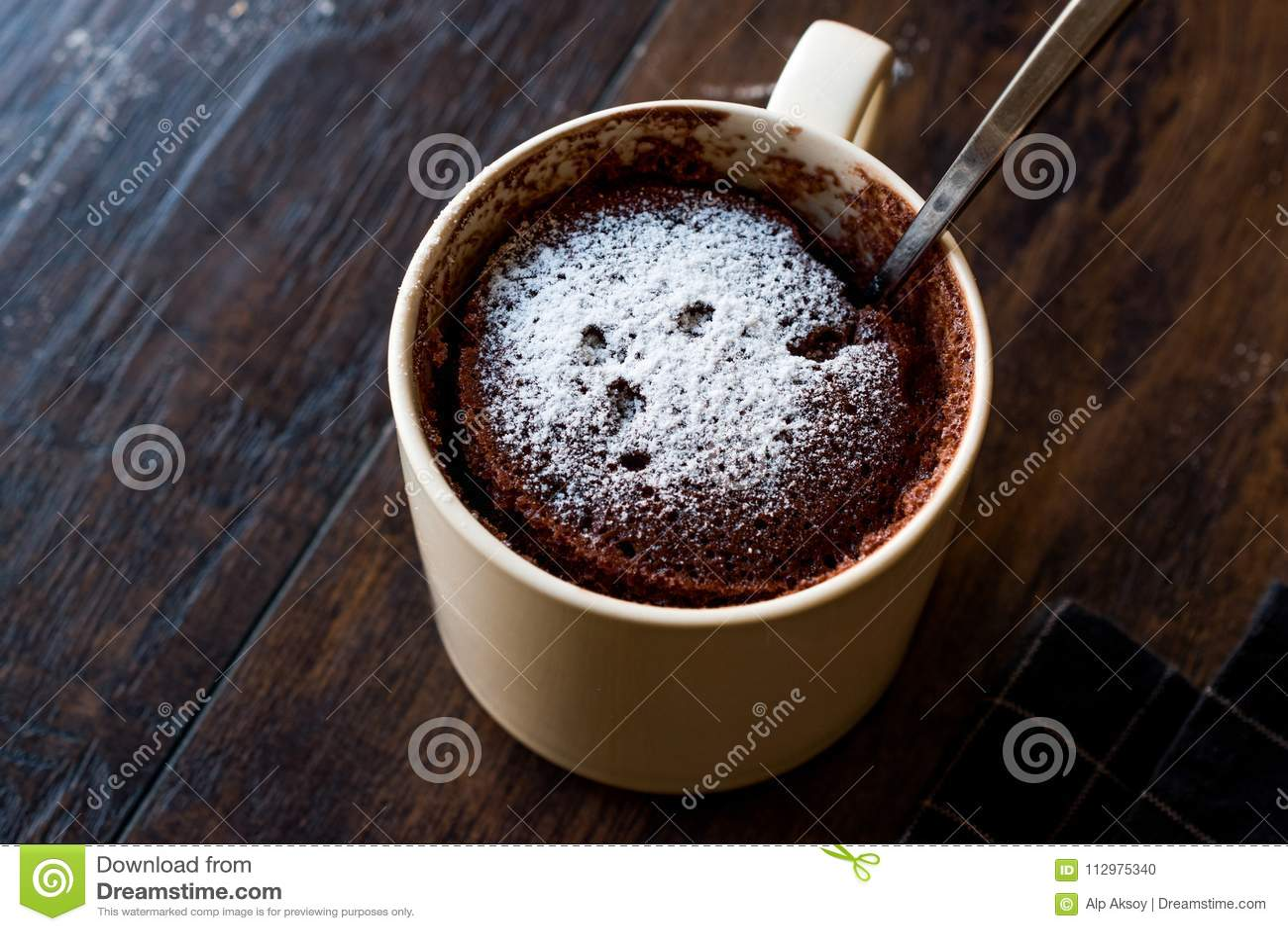 Microwave Brownie Chocolate Mug Cake with Powder Sugar on Dark Wooden Surface.