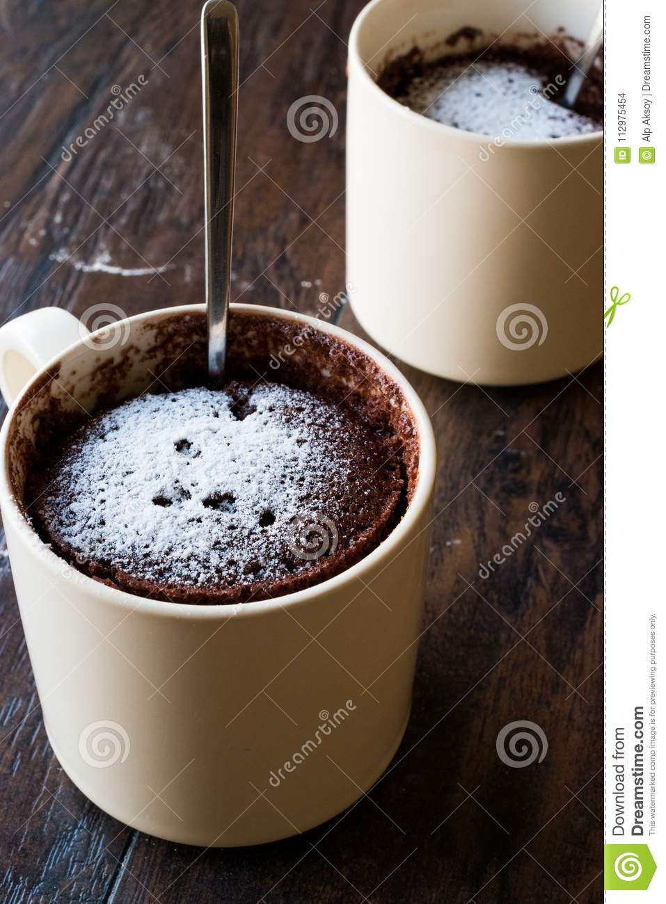 Microwave Brownie Chocolate Mug Cake with Powder Sugar on Dark Wooden Surface.