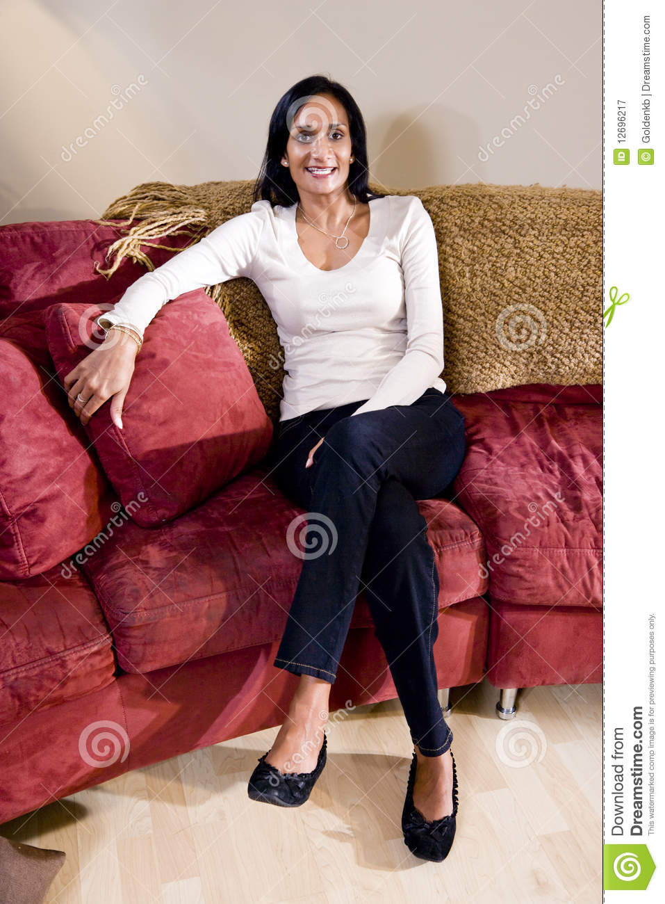 Mid Adult Indian Woman Sitting On Sofa Royalty Free Stock