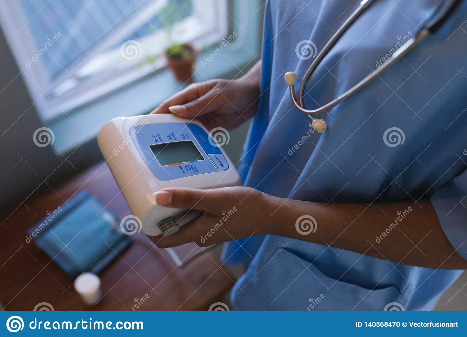 Female doctor holding blood pressure monitor at home
