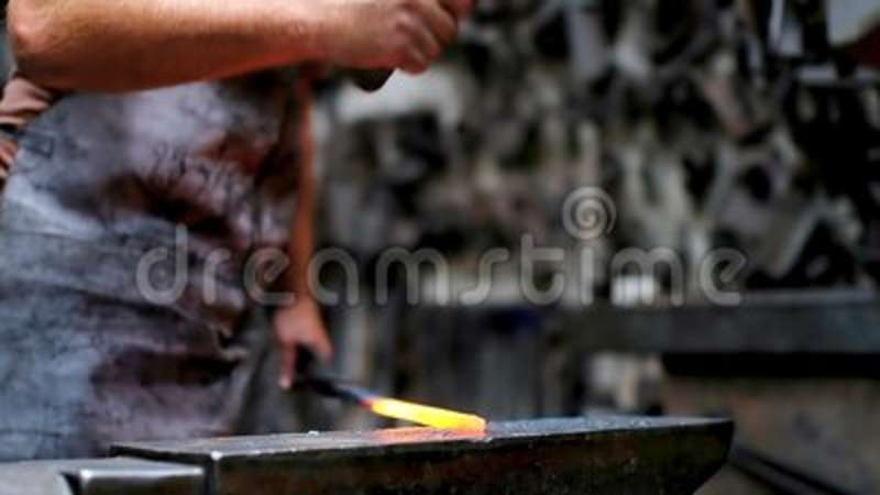 Blacksmith forging the molten metal with hammer
