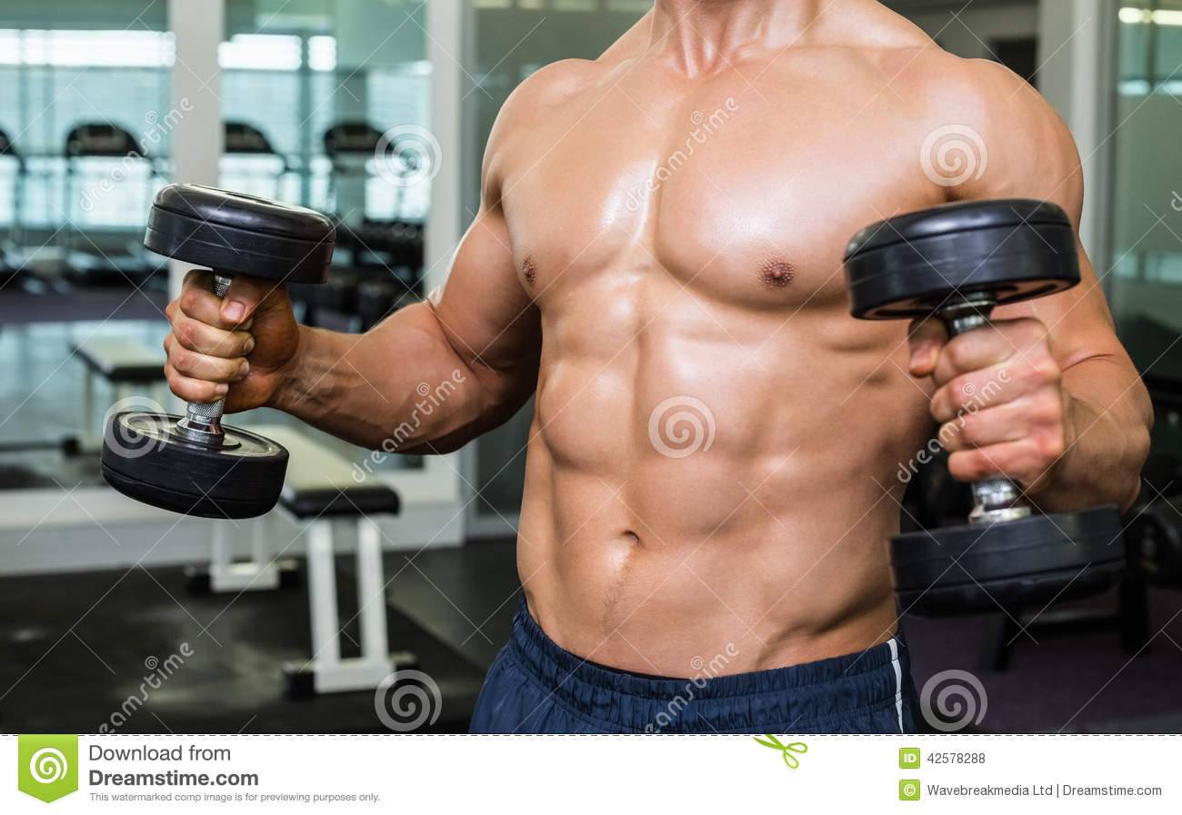 Athletic Muscular Young Man With Dumbbells On Bright