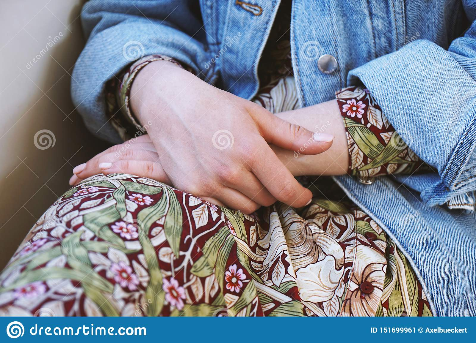 Mid section of young woman wearing denim jacket over summer dress with floral pattern