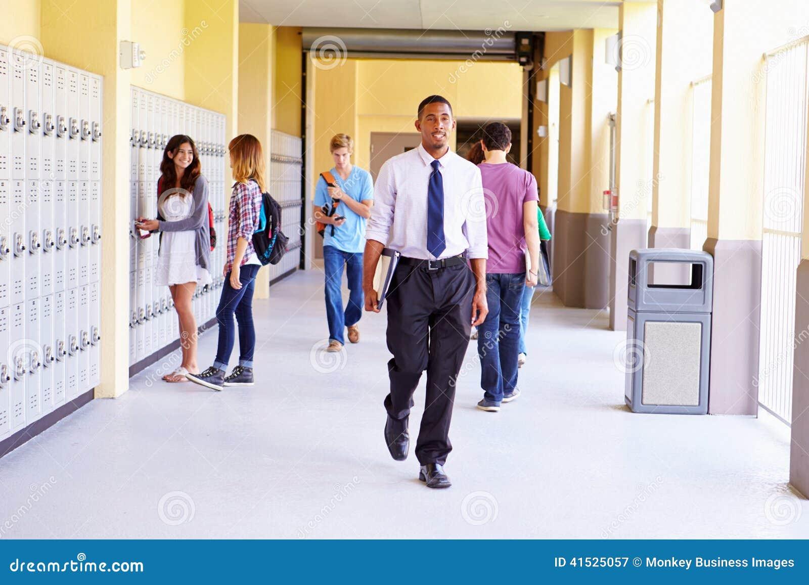 Middelbare schoolstudenten en Leraar Walking Along Hallway