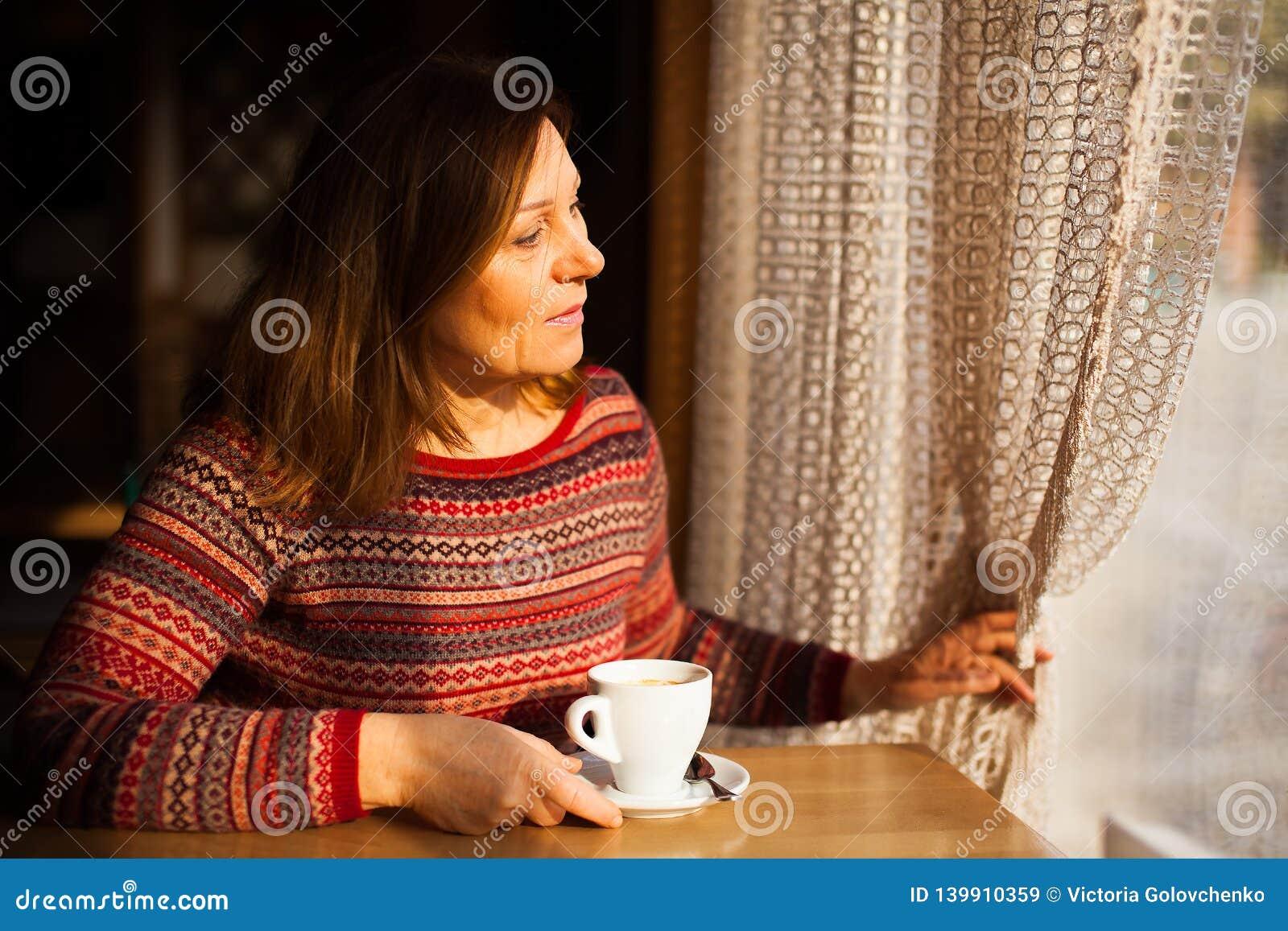 Midden oude dame die in gestreepte sweater door het venster met een kop van koffie kijken