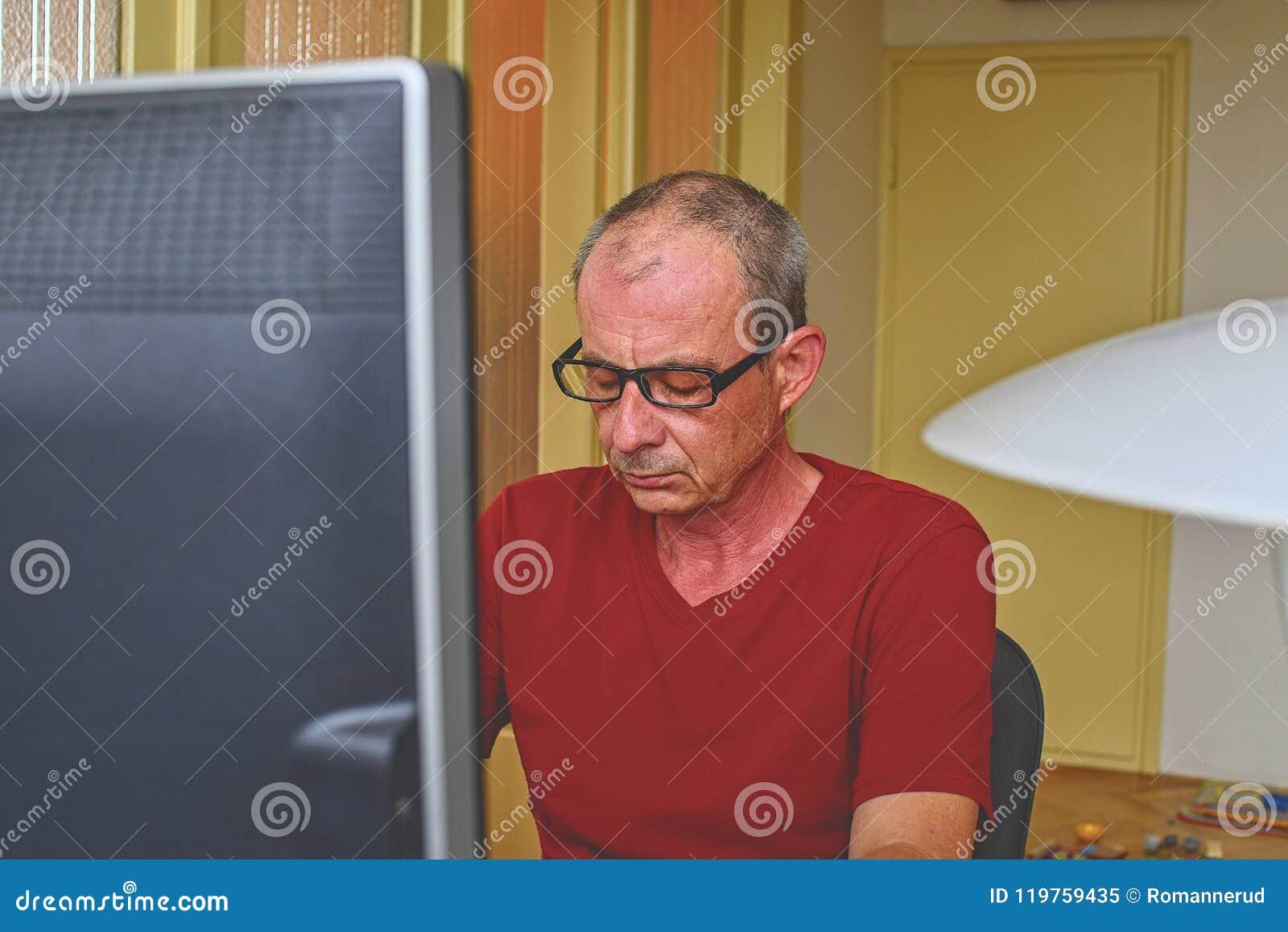 Midden oude mens die met glazen bij bureau zitten Rijpe mens die personal computer met behulp van Hoger concept Mens die thuis bu