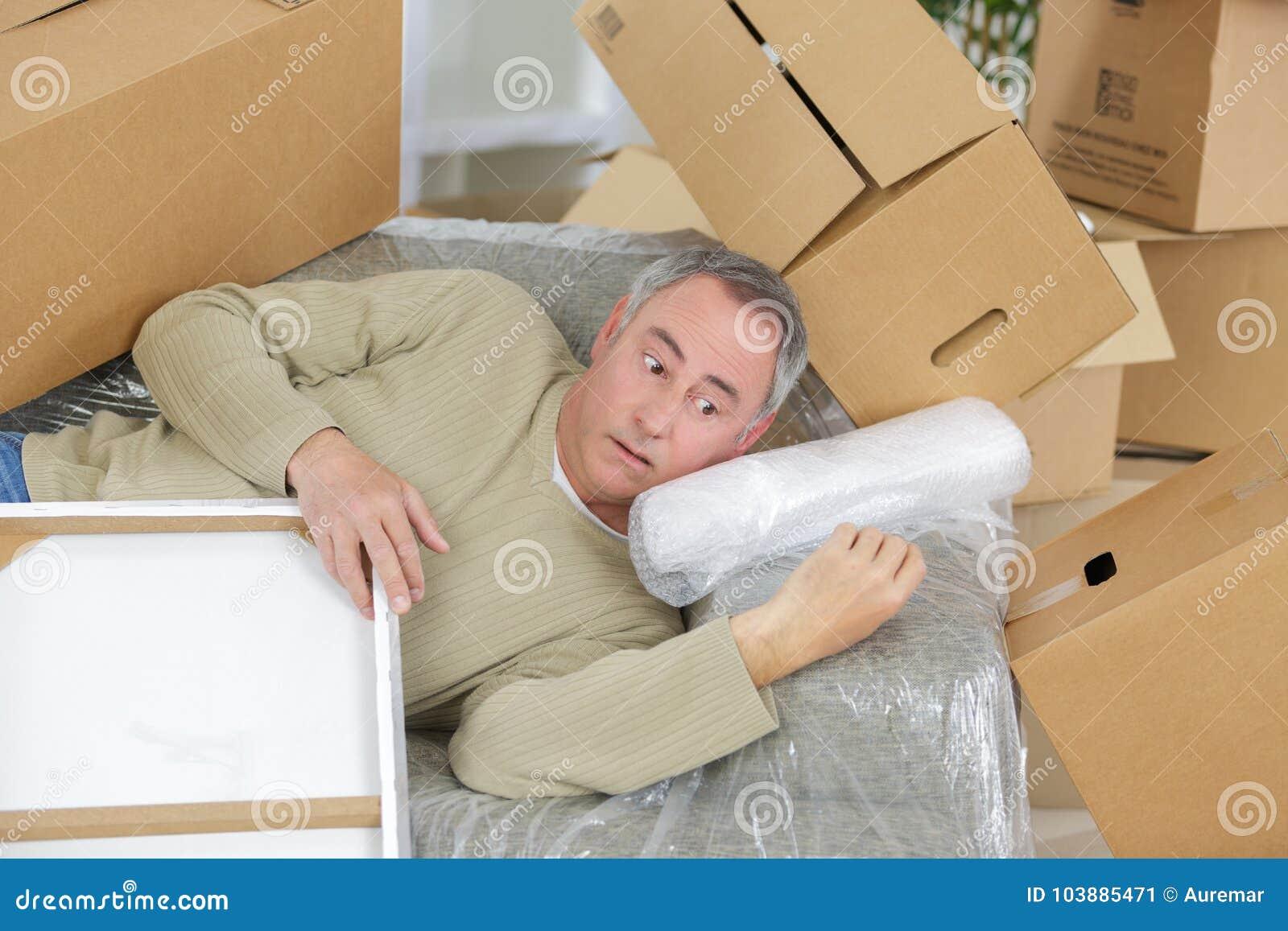 Midden oude mens in het midden van stapels precaire dozen