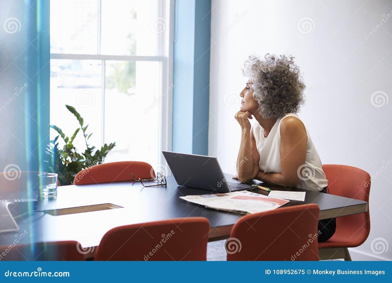 Midden oude vrouw die uit het venster in de bestuurskamer kijken