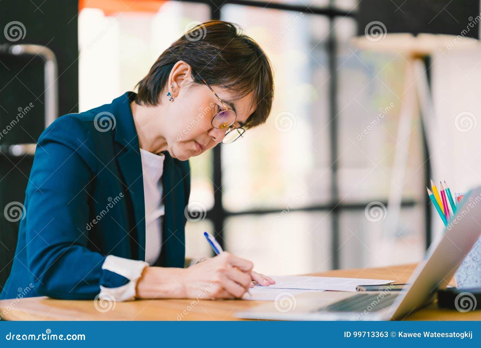 Middenleeftijds Aziatische vrouw die aan administratie in modern bureau, met laptop computer werken Bedrijfseigenaar of onderneme