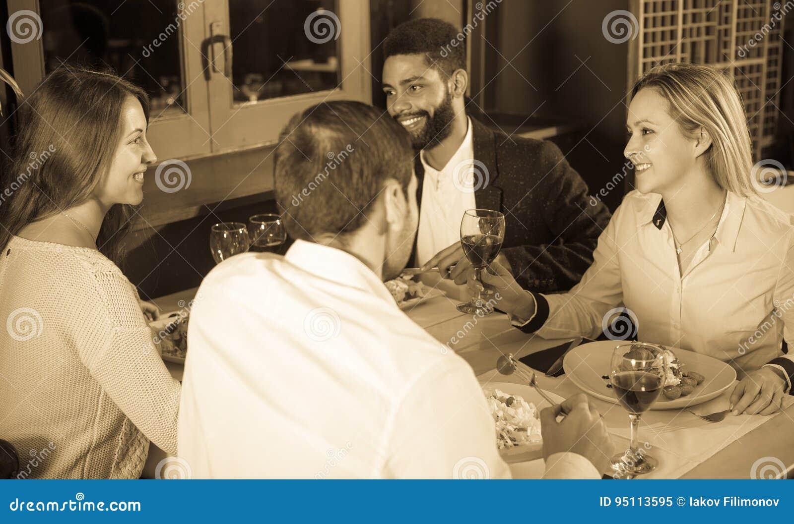 Middenstandmensen die van voedsel genieten