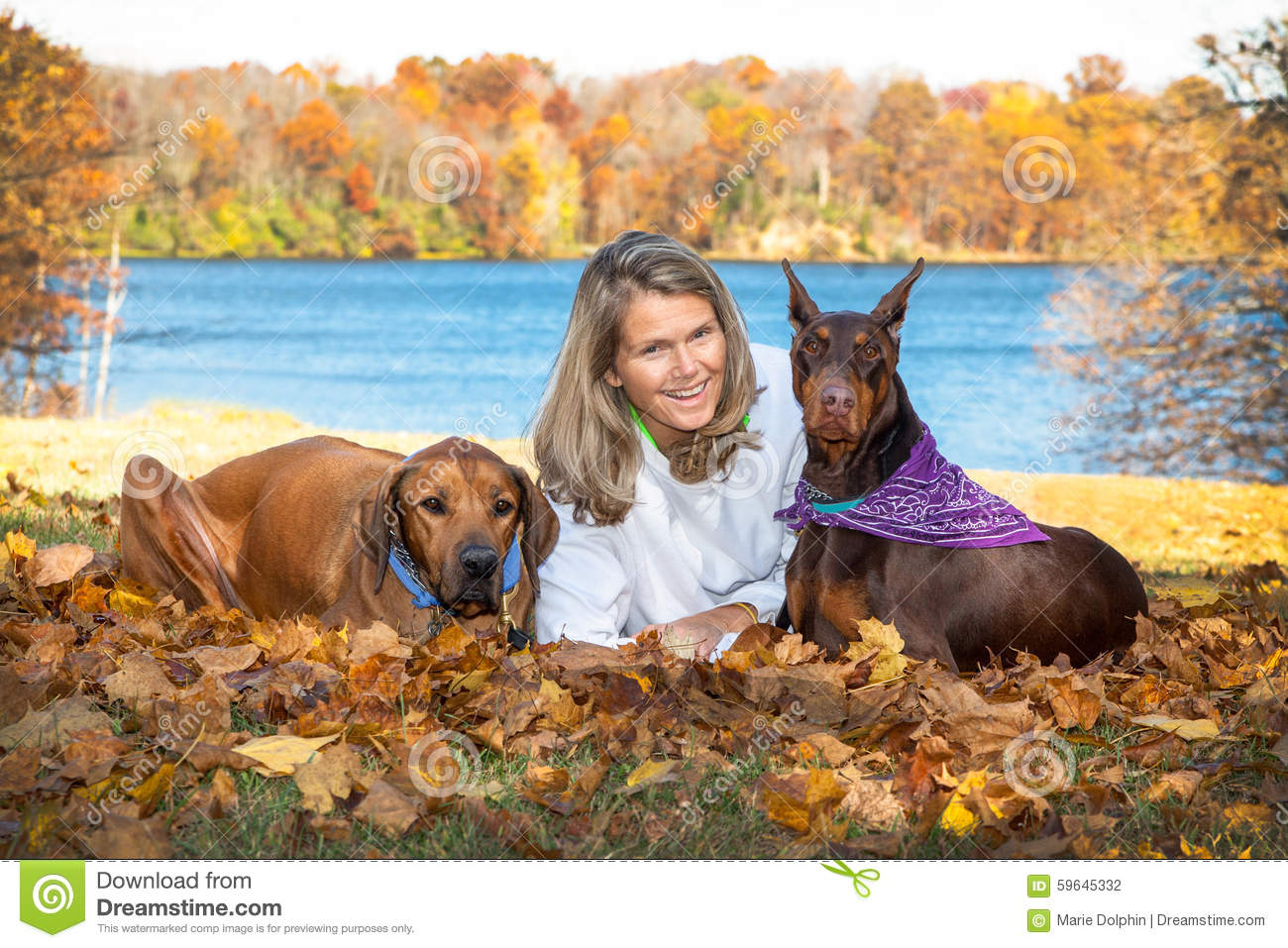Middle age attractive woman relaxing at the lake with her 2 large pet dogs