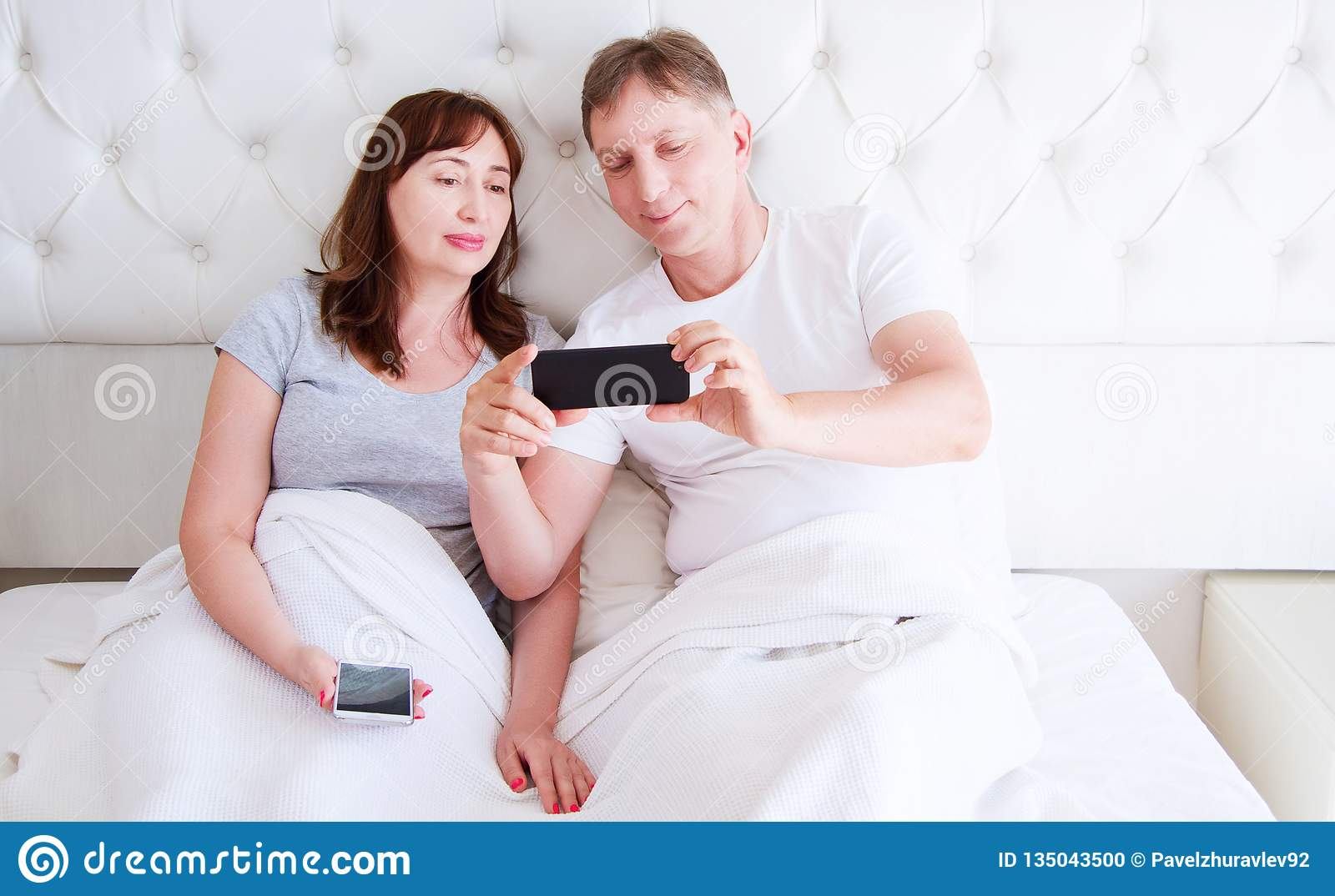 Middle age couple, woman and man using smartphone at bedroom. Ultra wide home shot