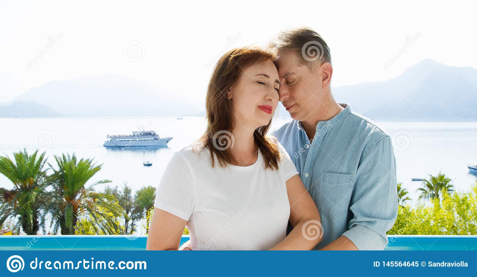 Middle age family couple on vacation resort on sea background. Summer people travel to tropical beach. Summertime leisure