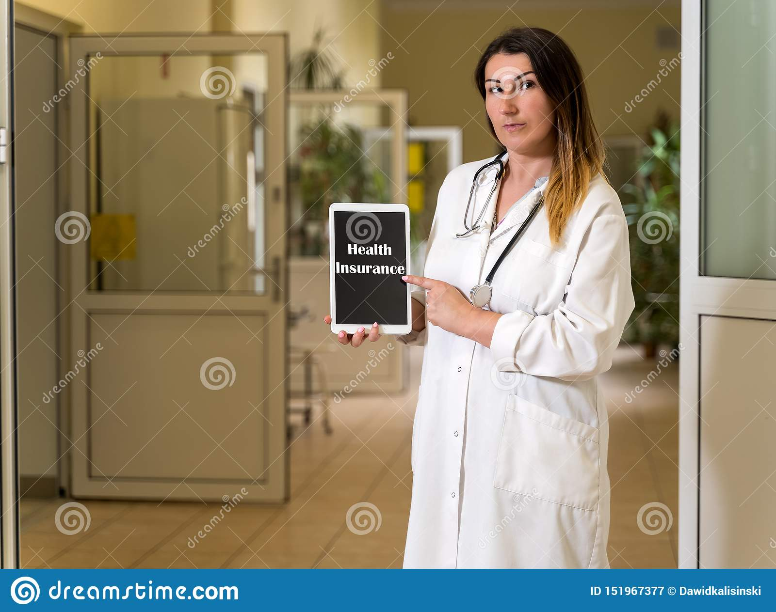 Middle age female doctor in white robe holding and pointing to tablet with Health Insurance text