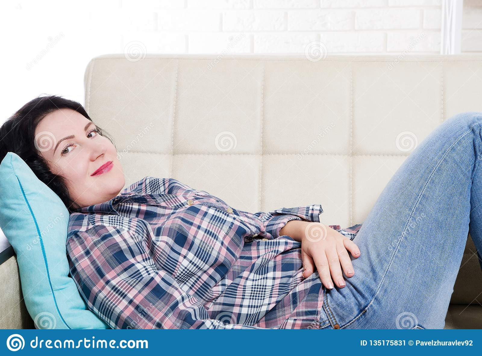 Middle age smiling woman lies on sofa and looking. Young brunette woman thinking at home in a leisure time