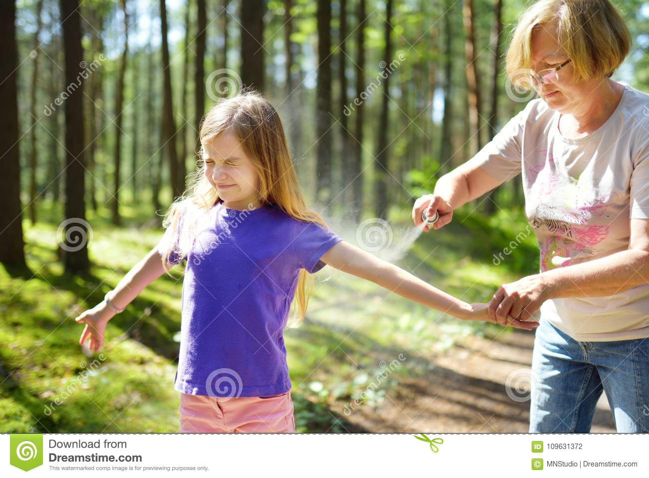 Middle age woman applying insect repellent to her granddaughter before forest hike beautiful summer day. Protecting children from