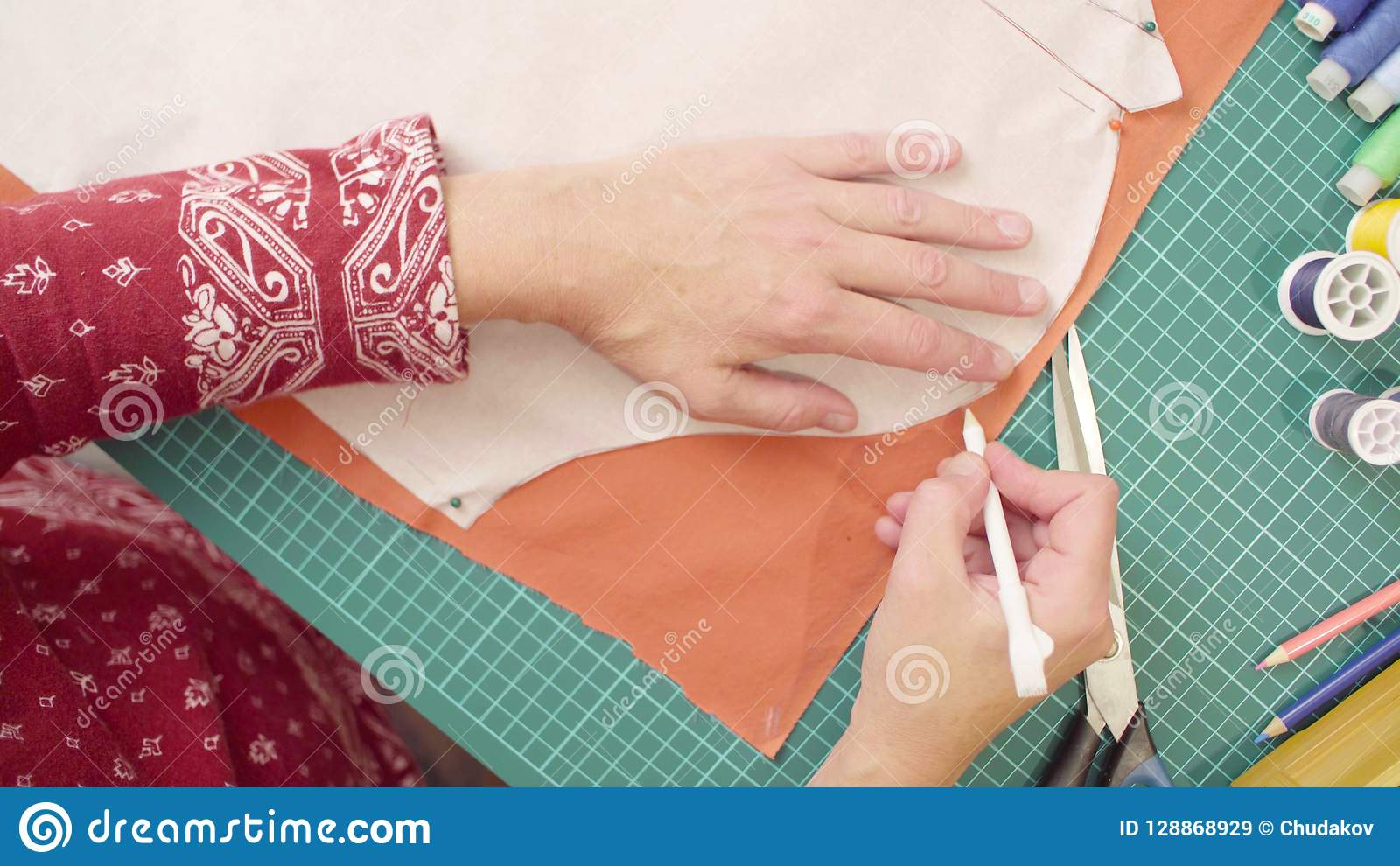 Middle-age woman hands drawing outline of a paper pattern with a pencil