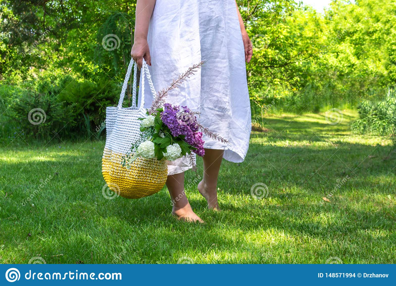Middle age woman in white simple linen dress stays barefoot on the grass in beautiful garden and holds knitted white-yellow bag