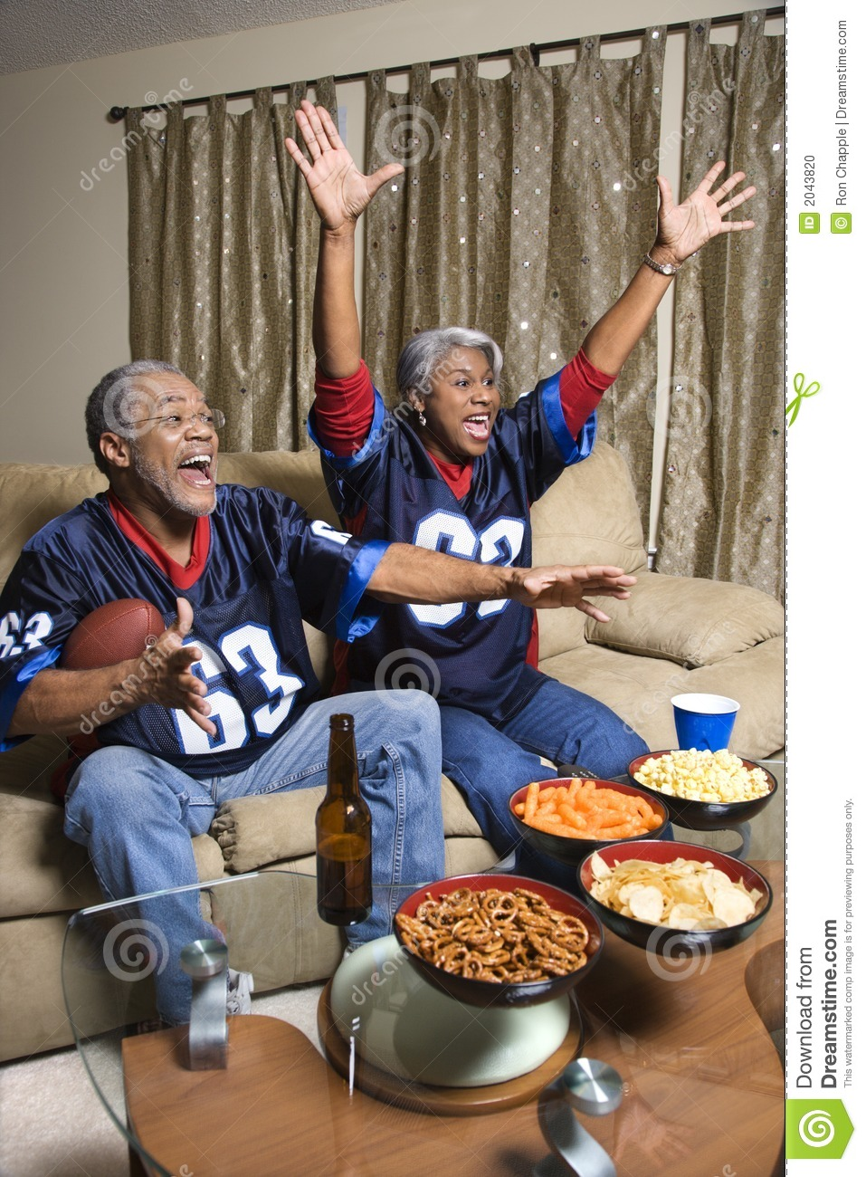 Middle-aged African-American Couple Watching Sports On Tv ...