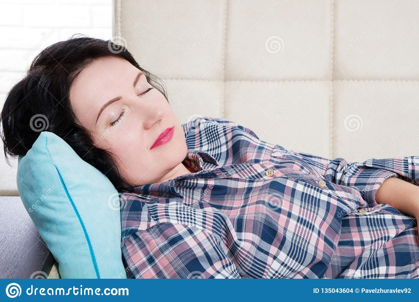 Middle aged beautiful woman lying in sofa sleeping at home after hard working day tired. Sweet dreams, good morning, new day