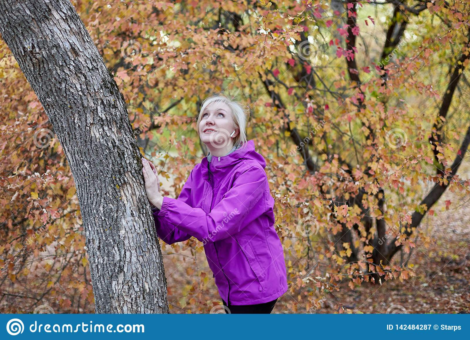 Middle aged caucasian woman stands alone near to the tree at autumn park. Hands on the tree, bright casual wear, white wireless ea
