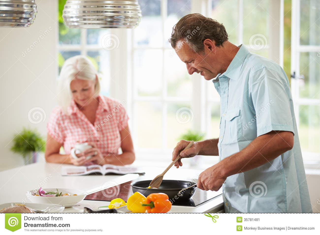 Middle Aged Couple Cooking Meal In Kitchen Together
