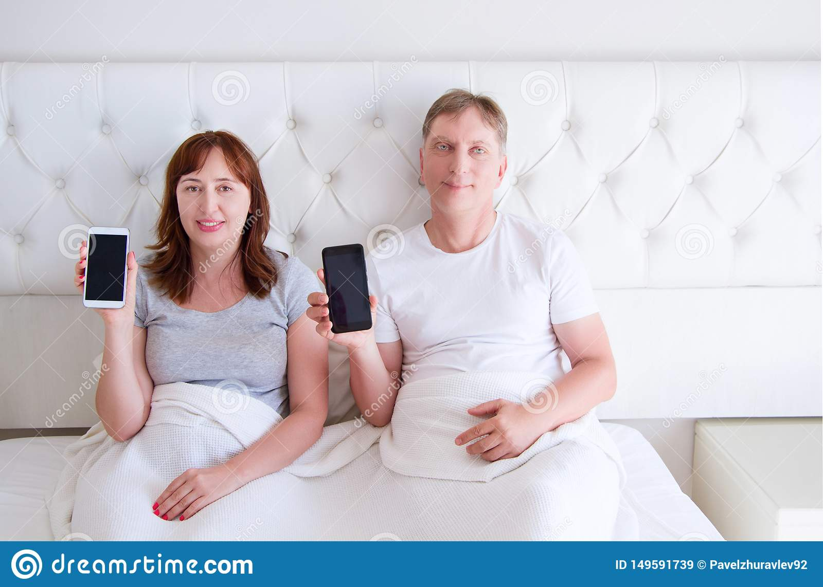 Middle aged couple holding blank screen mobile phone and lying on bed in hotel room bedroom