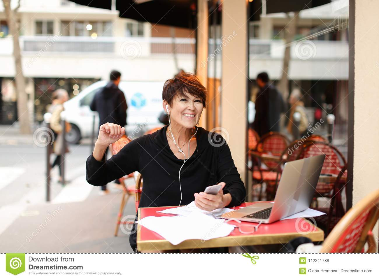 middle-aged female tourist listen music by smartphone and danci