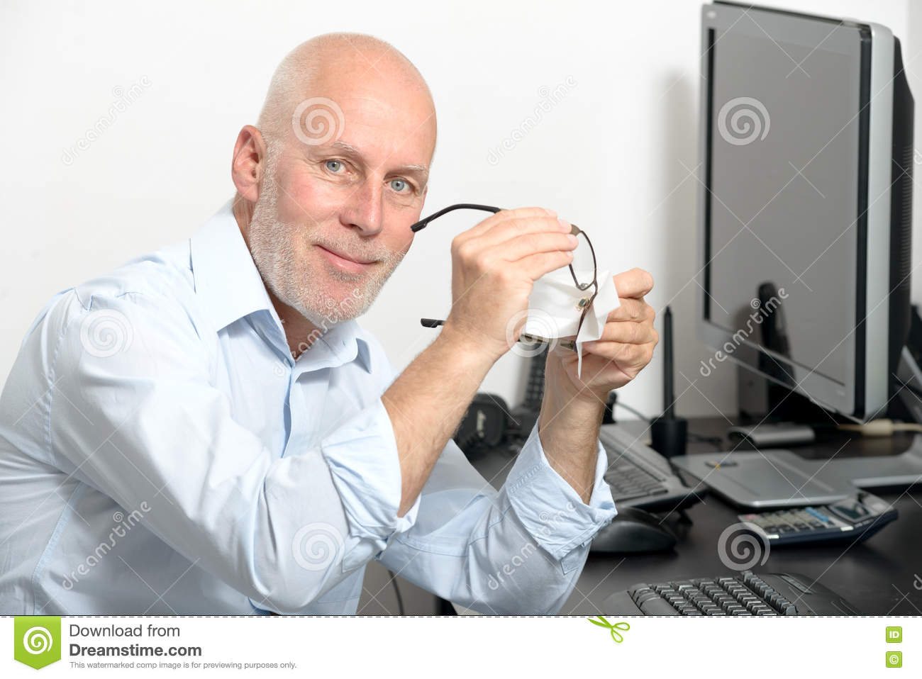 Middle-aged man cleans his glasses in his office