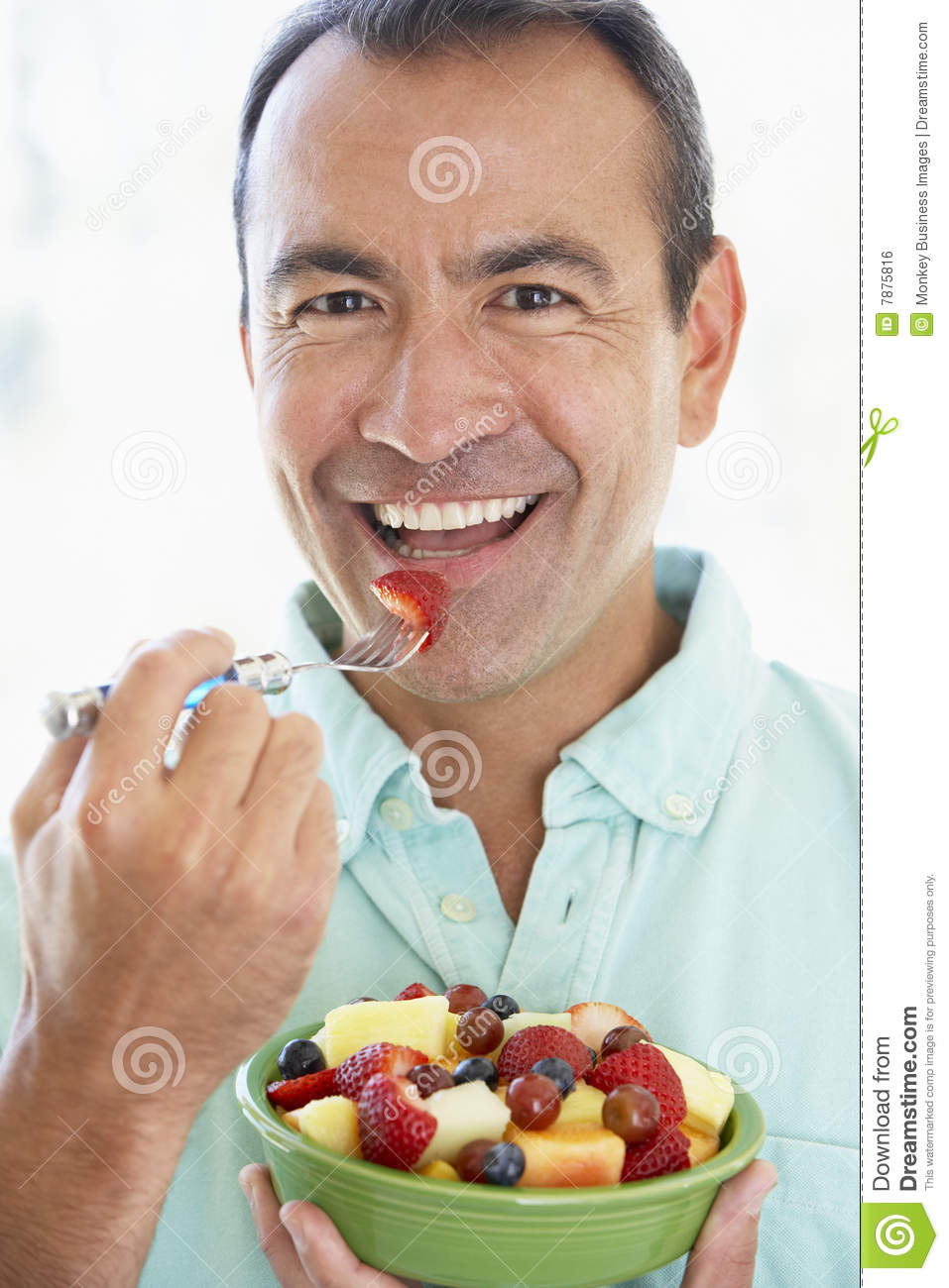 middle aged man eating fresh fruit salad 7875816 men laughing alone with salad