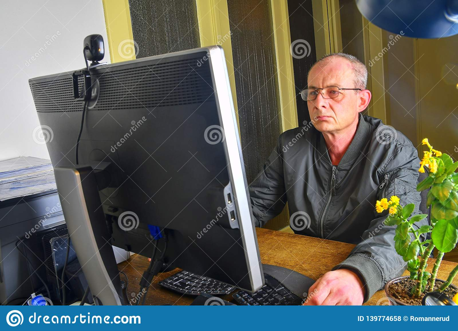 Middle aged man with glasses sitting at desk. Mature man using personal computer. Senior concept