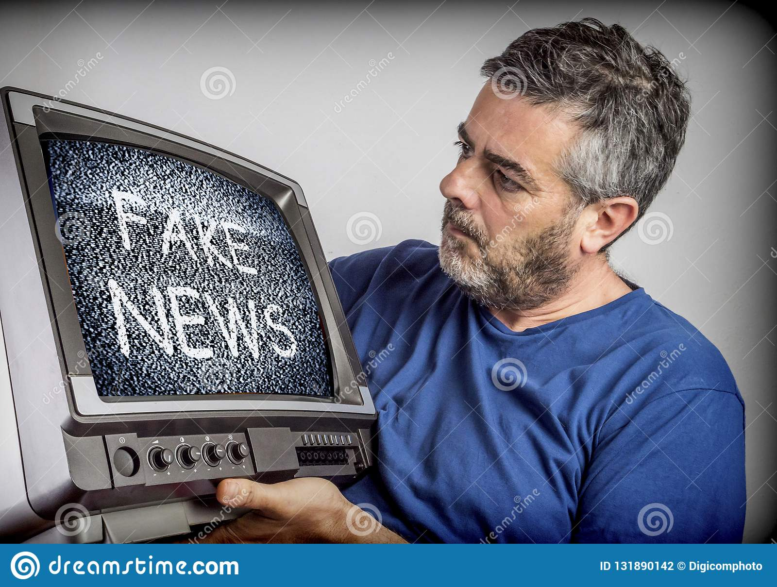 Middle-aged man holds a TV with fake news screen, conceptual ima. Ge stock photography