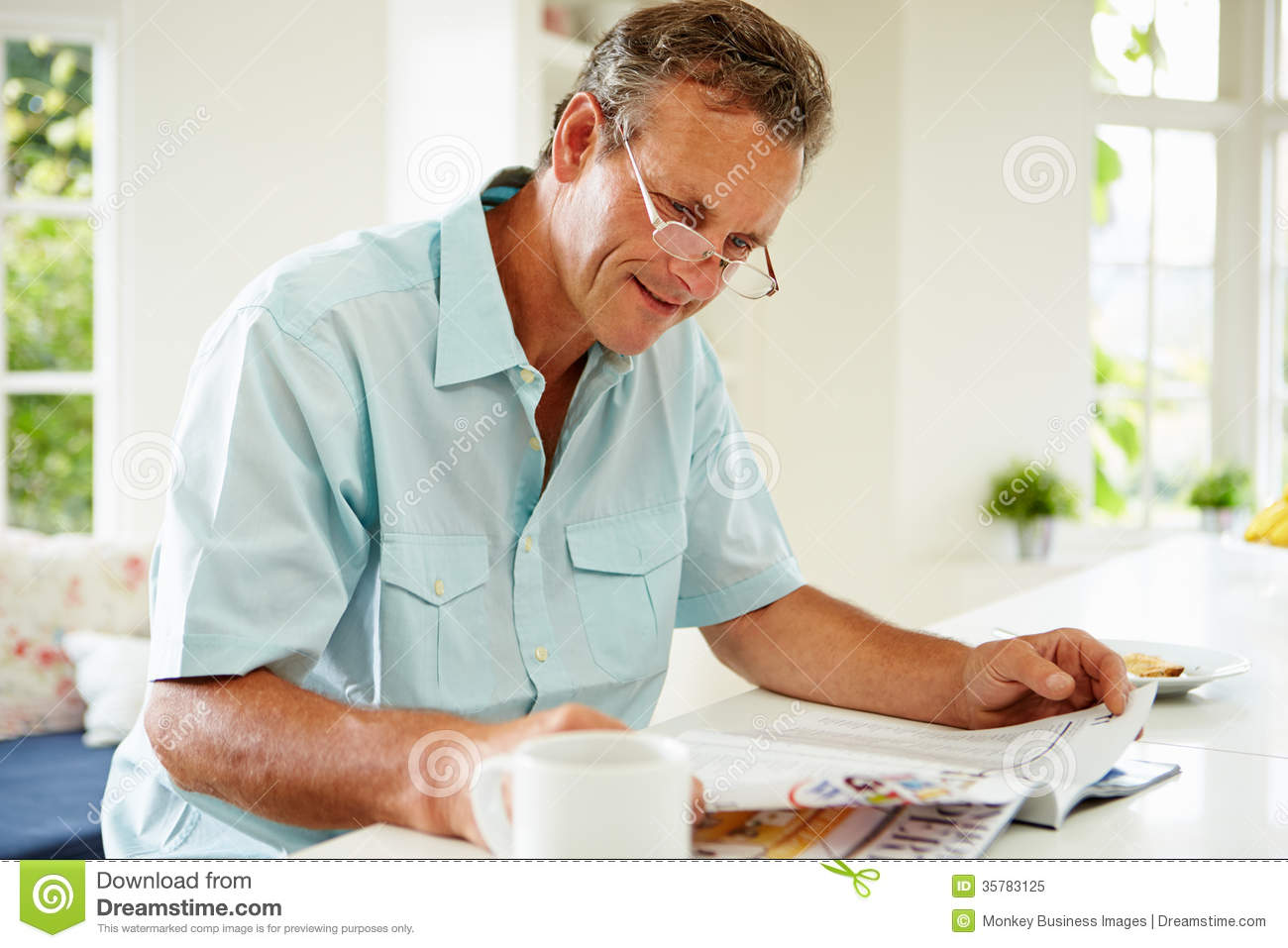 Middle Aged Man Reading Magazine Over Breakfast Stock Image