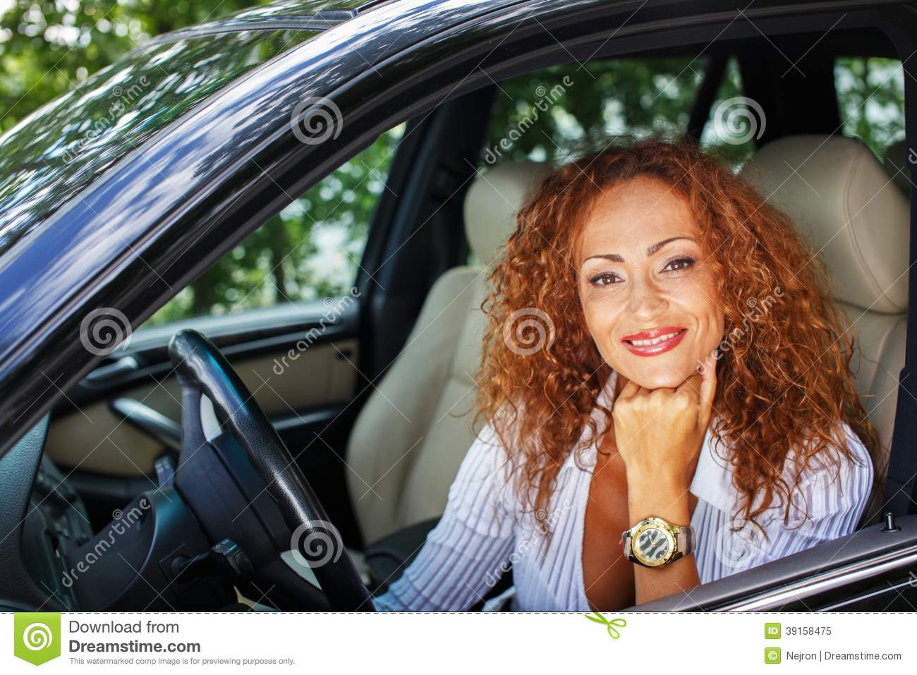middle-aged redhead woman in car stock image - image of mature