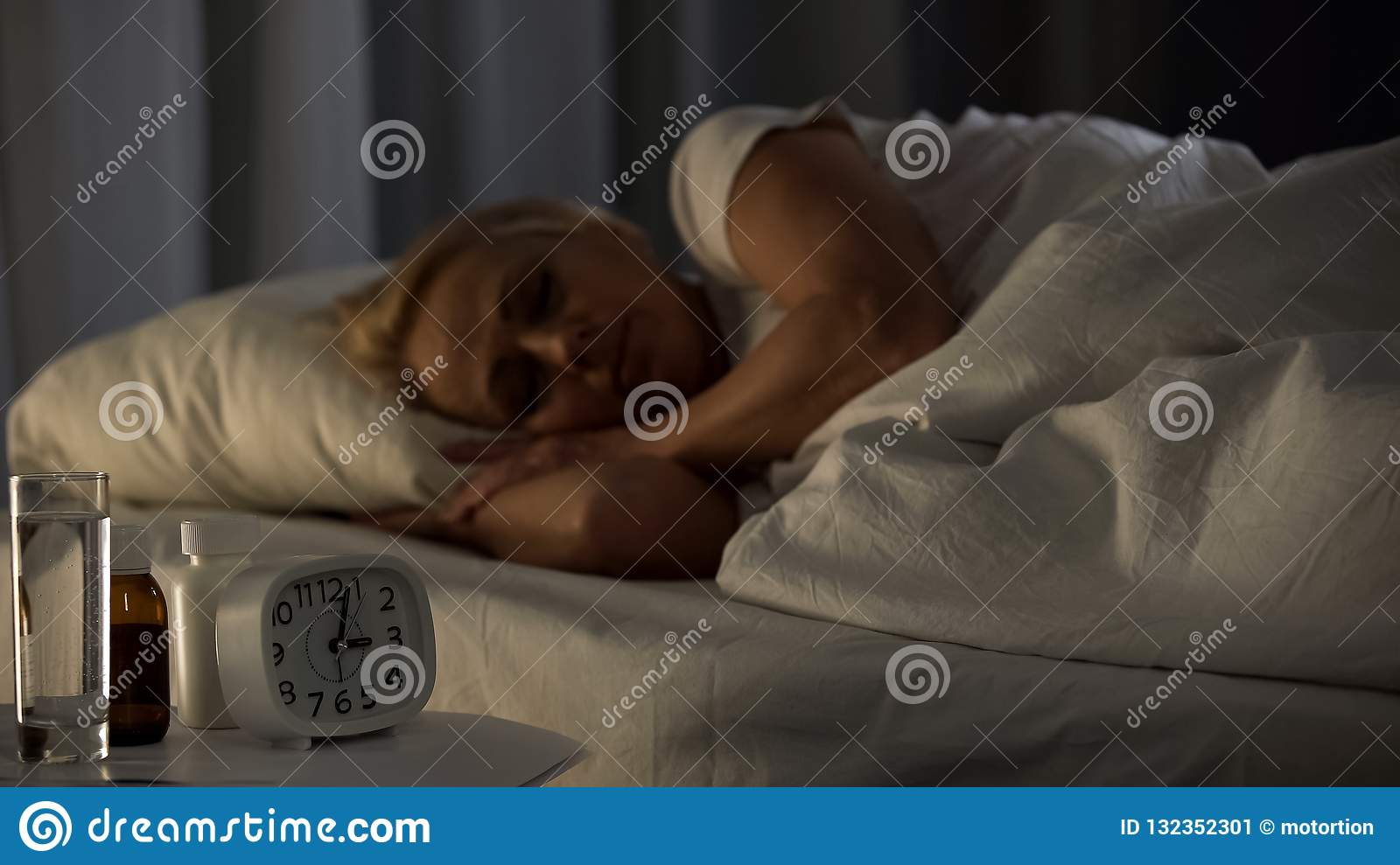 Middle-aged sick lady sleeping with pills and water glass on table, health