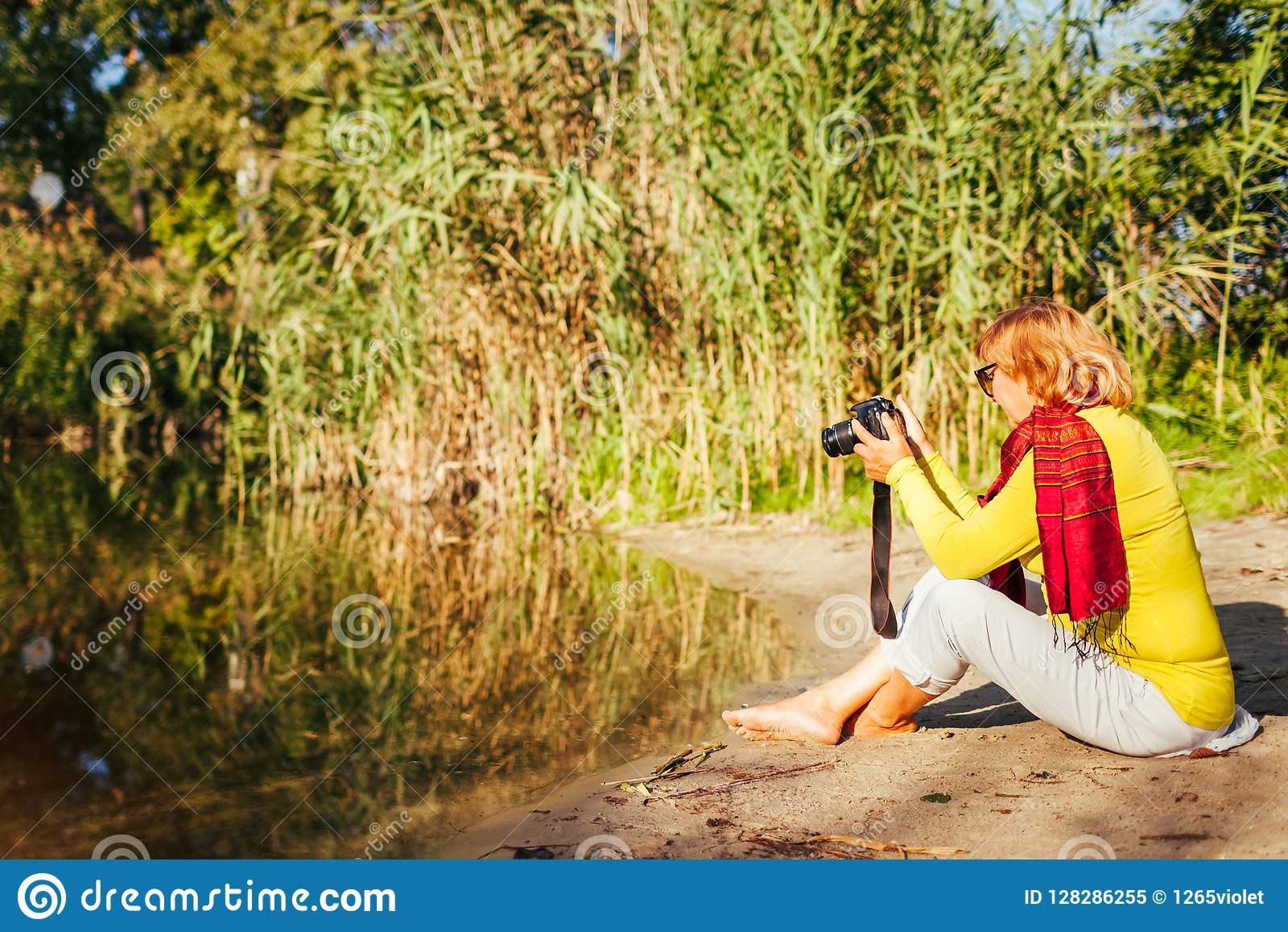 Middle-aged woman checking images on camera sitting by autumn river bank. Senior woman enjoying hobby